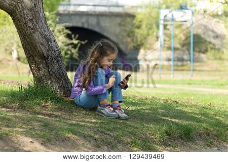 Cute little girl sitting on the grass in a park with a mobile phone in her hands and using modern smartphone
