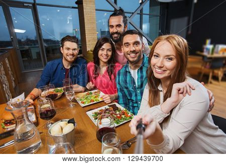 leisure, technology, friendship, people and holidays concept - happy friends having dinner and taking picture by smartphone selfie stick at restaurant