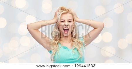 emotions, expressions, hairstyle and people concept - smiling young woman or teenage girl holding to her head or touching hair over holidays lights background