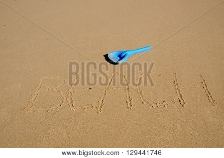The word beach written in the sand with a spade