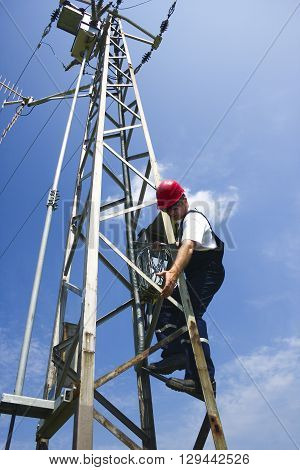 Electrician in red helmet working on electric power pole ** Note: Visible grain at 100%, best at smaller sizes
