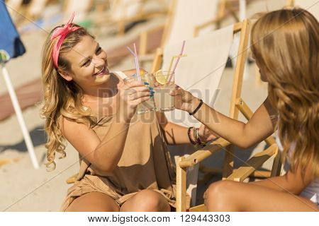 Two beautiful young girls lying on a sunbed on the beach cheering with a lemonade and chatting