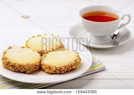 Butter cookies (alfajores) with caramel and peanut and cup of tea on wooden background.