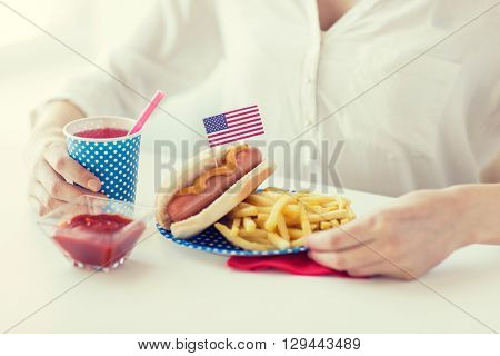 national holidays, celebration, food and patriotism concept - close up of woman eating hot dog and french fries with drink in disposable paper cup at 4th july at party on american independence day