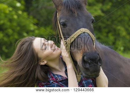 Smiling young girl with long hair love her mare