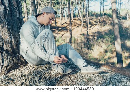 Sporty young man tying shoelaces outdoor near a tree in the forest