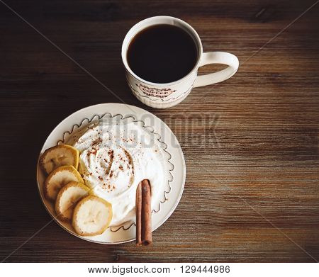 The Cottage Cheese with pieces of Banana,Sticks of Cinnamon and Cap of Coffe on the Wooden Table,Toned
