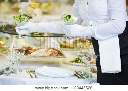 Restaurant services. Female waitress serving table