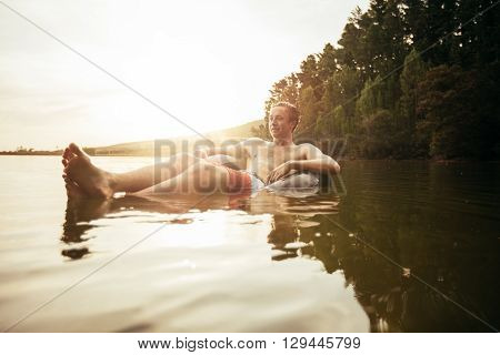 Portrait of young man in lake on inflatable ring. Man relaxing in water on a summer day.