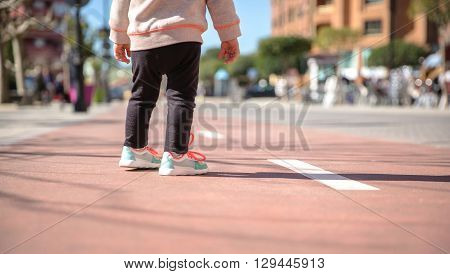 Back view of little girl legs with sneakers and black leggins standing over a city runway on a sunny day