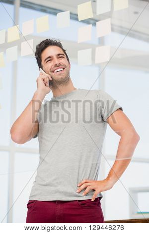 Man talking on phone with hand on hip in office