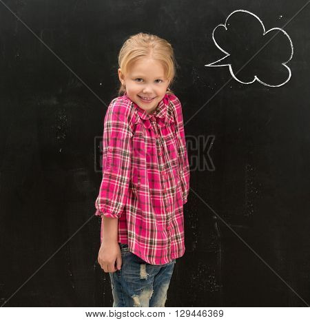 cute smiling little schoolgirl standing in front of the blackboard with drawn phrase cloud on it
