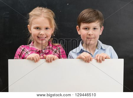 two cute smiling schoolchildren with blank sheet of paper in hands