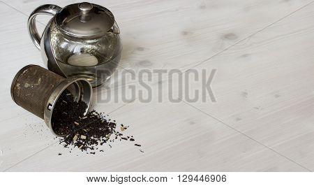Dry tea and teapot at white wooden background