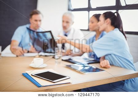 Digital tablet and file on table in conference room and medical team interacting in background