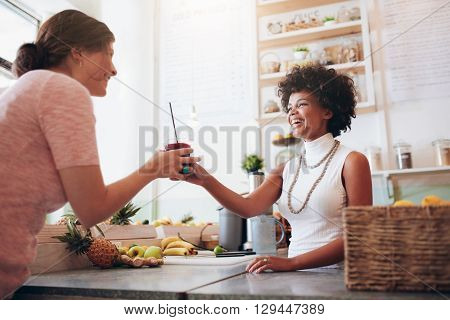 Female Bartender Serving A Glass Of Fresh Juice To Customer