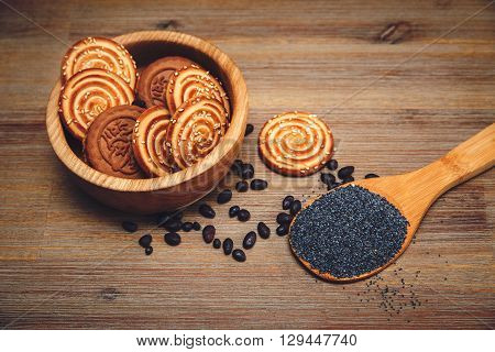 There are Pieces of Roll with Poppyseed and Cookies,Halavah and Chocolate Peas.Tasty Sweet Food on the Wooden Background,Toned