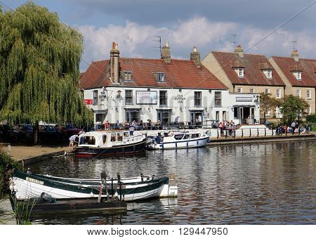 ELY, UK - SEPTEMBER 20: People walk alongside the River Great Ouse and eat on the patio of a riverside pub in the small tourist town of Ely, Cambridgeshire on September 20 2015.