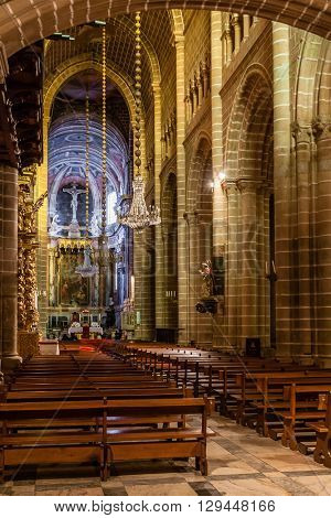 Evora, Portugal - December 1, 2015: Nave and altar of the Evora Cathedral, the largest cathedral in Portugal. Romanesque and Gothic architecture. UNESCO World Heritage Site.