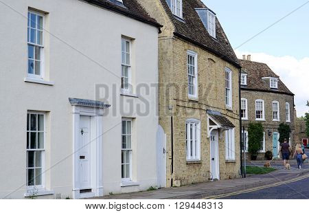 ELY, UK - SEPTEMBER 20: A couple walk their dog along a residential street of detached period houses in the centre of the small, historic cathedral city of Ely, in Cambridgeshire, England on September 20, 2015.