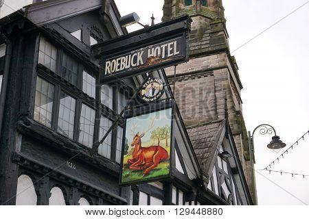 LEEK, UK - DECEMBER 31: A brightly-painted sign for the Roebuck Hotel hangs from a historic wattle and daub building along the high street in Leek, a market town in the Staffordshire Moorlands, England, on December 31, 2015.