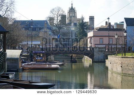 CAMBRIDGE, UK - FEBRUARY 24: Tourists punt down river and pedestrians walk down Bridge Street in the historic centre of the university city of Cambridge, England on February 24, 2016.