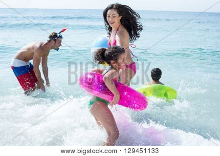 Happy family with swimming ring playing in sea