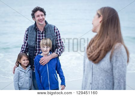 Smiling father with children looking at mother on sea shore