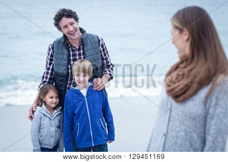 Happy father with children looking at mother while standing on shore