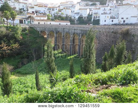 Arched road bridge over valley in mountains in Andalucia