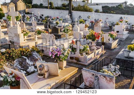 Crato, Portugal. December 12, 2015: Typical Catholic cemetery with the graves decorated with flowers in the interior south of Portugal.