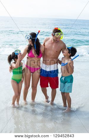 Family wearing diving goggles while standing on sea shore at beach