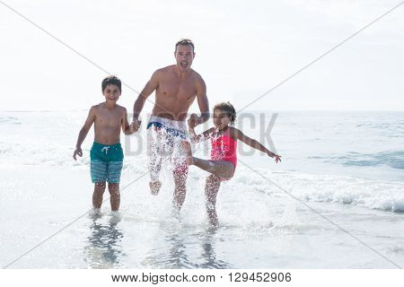Cheerful father enjoying with children in shallow water at beach