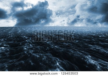 Rough blue ocean against blue sky with white clouds