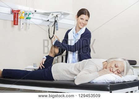 Happy Physiotherapist Helping Senior Woman With Leg Exercise
