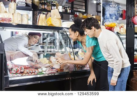 Couple Choosing Product From Display Cabinet While Saleswoman As