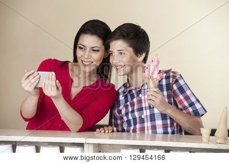Woman Taking Self Portrait With Son Holding Strawberry Ice Cream
