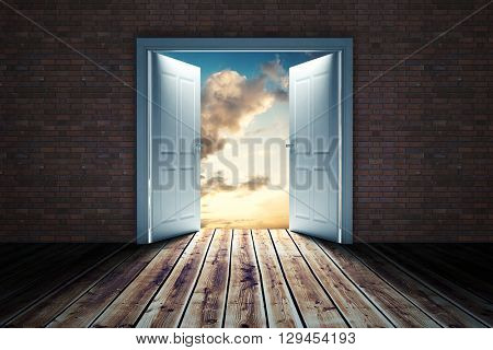 Door opening in dark room to show sky against blue and orange sky with clouds