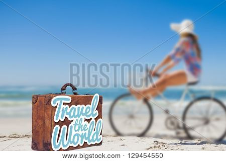 Travel the world message on an old suitcase against woman riding bike