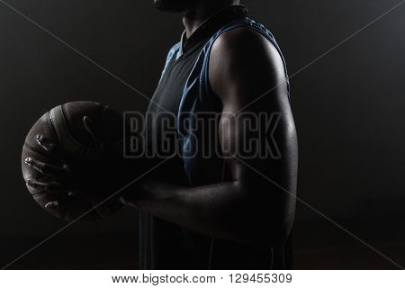 Zoom on a side of a basketball player holding a basketball against a black background