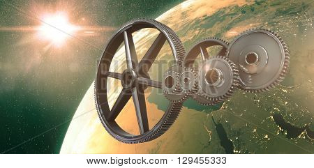 Metal cogs and wheels connecting against aerial view of the earth