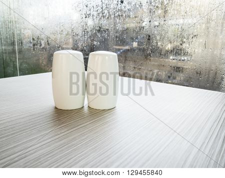 Salt and pepper bottles on wood table with water drop on glass background (kitchen shakers)