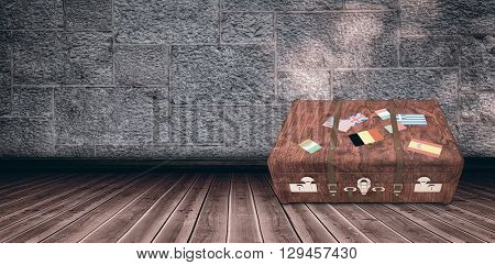 Suitcase with stickers against wooden floor