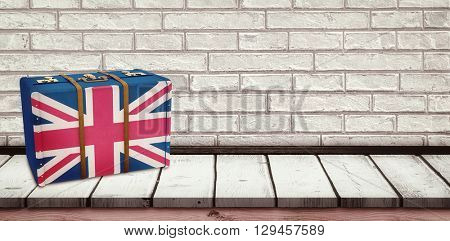 Great Britain flag suitcase against wooden board
