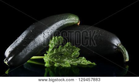Studio shot of two zucchinis on black background