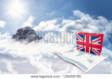 Great Britain flag suitcase against mountain peak through the clouds