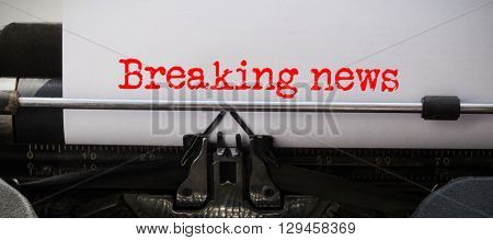 Words breaking news against white background against close-up of typewriter