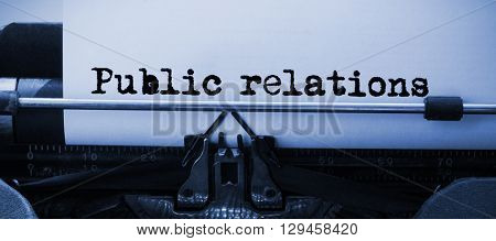 Words public relations against white background against close-up of typewriter