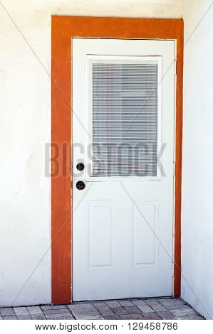 A white residential door is closed with large window and framed in orange trim on white wall.