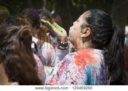 NEW YORK - APR 30 2016: A woman with colorful powder on her face celebrates by blowing green powder into the air at the Holi Hai Festival of Colors hosted by NYC Bhangra in New York on April 30 2016.